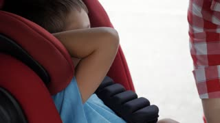 Positive mother fastens seat of infant car seat