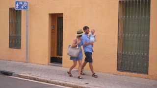 Positive parents walking with little baby along the street