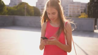 Positive teenager texting on phone while walking on street