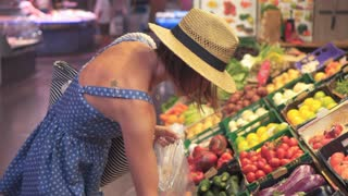 Positive woman customer picking vegetables at marketplace