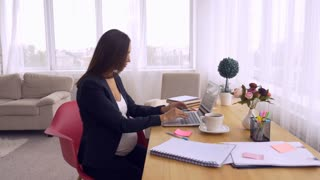 Pregnant businesswoman typing on keyboard of laptop