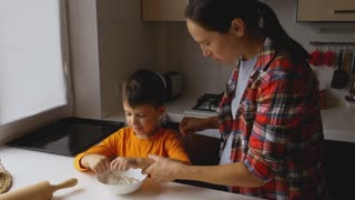 Pregnant mother helping son preparing the dough for cookies