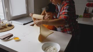 Pregnant mother helping son rolling out dough for chocolate cookies