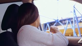 Pregnant woman buckling seat belt in car