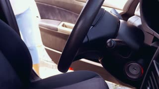 Pregnant woman fastening seat belt before driving car