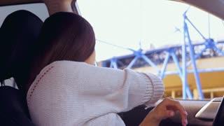 Pregnant woman in driver seat adjusting seat belt