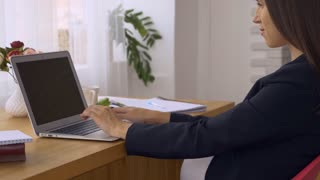 Pregnant woman typing on keyboard of laptop