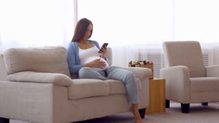 Pregnant woman using phone and caressing her belly