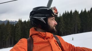 Relaxed bearded man admiring the panorama with ski slopes