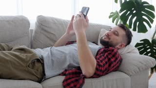 Relaxed male lying down the sofa and using phone