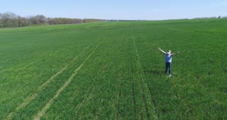 Relaxed senior man spreads arms while standing on green field