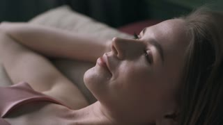 Relaxed woman waking up early in bed