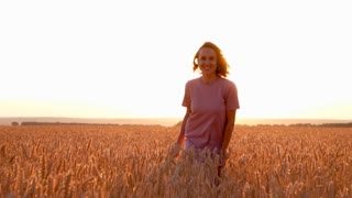 Relaxed woman walking in wheat field at sunset