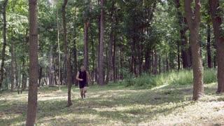 Runner with earphones listening music running in the forest