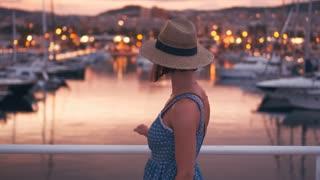 Sensual woman walking along quay at the sunset