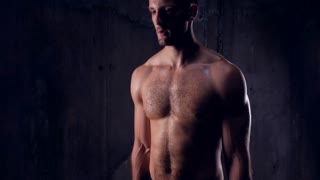 Sexy bare-chested male athlete with dumbbells pumping up biceps