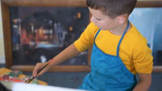 Skilled boy in apron painting on easel at art school