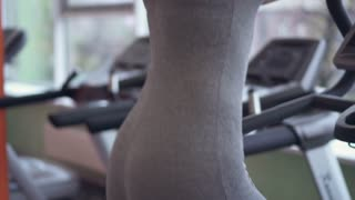 Slim woman exercising on step machine at the gym
