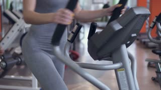 Slim woman using cross trainer at the gym