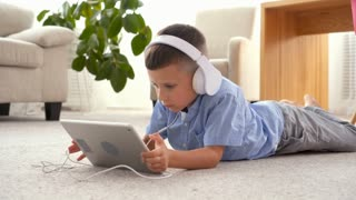 Small boy in headphones using tablet