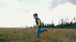 Small boy running in Carpathian mountains
