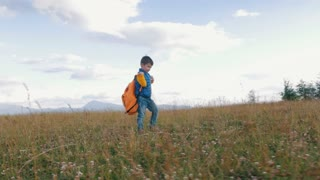 Small boy with heavy backpack walking in mountains