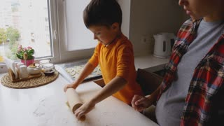 Small son rolling out dough for cookies, helping mother