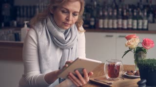Smiley mature woman using digital, tablet while drinking tea