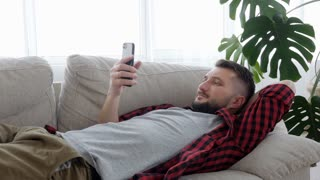 Smiling bearded male holding mobile telephone in hands while lying in bed
