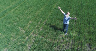 Smiling bearded man with outstretched arms standing on green field