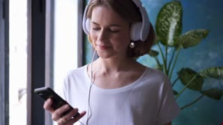 Smiling girl listening and choosing song at telephone