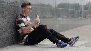 Smiling guy in headphones enjoying lunchtime outdoors