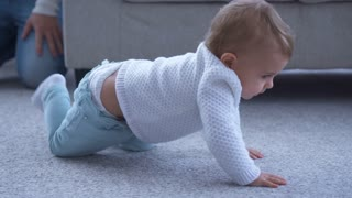 Smiling small girl crawling on the floor