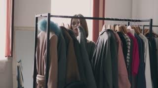 Smiling young woman choosing coat