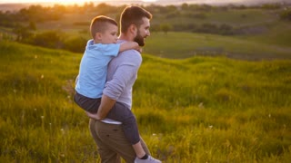 Son embracing father while sitting on his back walking in field