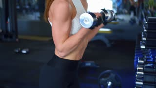 Sportive athletic woman with dumbbells pumping up biceps