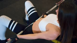 Sportive girl working out hip thrust with barbell