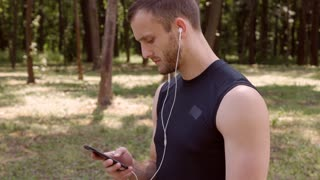 sportsman using a mobile phone to switch music on the playlist before running