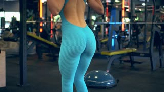 Sporty girl doing lunges with barbell