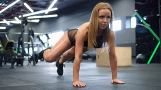 Sporty girl exercising in plank at gym