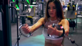 Strong fit sportswoman doing bicep cable curl