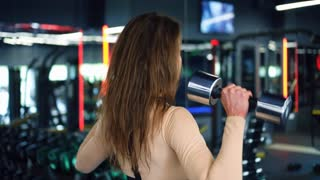 Strong girl lifting dumbbells in front of mirror