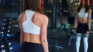 Strong girl working out with dumbbells in front of mirror