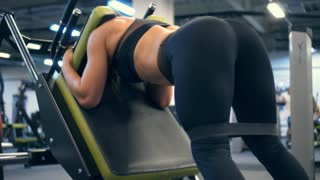 Strong woman exercising on reverse squat machine