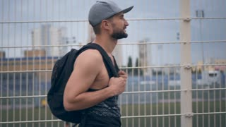 Stylish bearded man quickly walking and using mobile phone