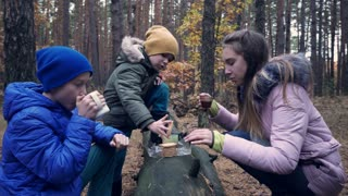 Three children drinking tea and eating some biscuits in forest