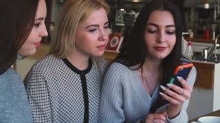 Three women friends looking something on phone and smiling