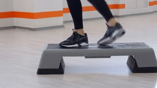 Tilt up and down of sporty instructor doing aerobics in a gym