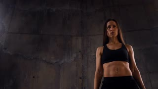 Training of female with perfect muscular body against dark wall