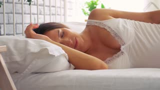 Tranquil woman sleeping on side in bedroom